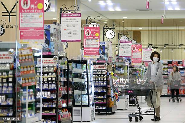 Customers push shopping carts at an Aeon Co supermarket in Chiba Japan on Tuesday April 1 2014 Japan's economy will probably withstand a sales tax...