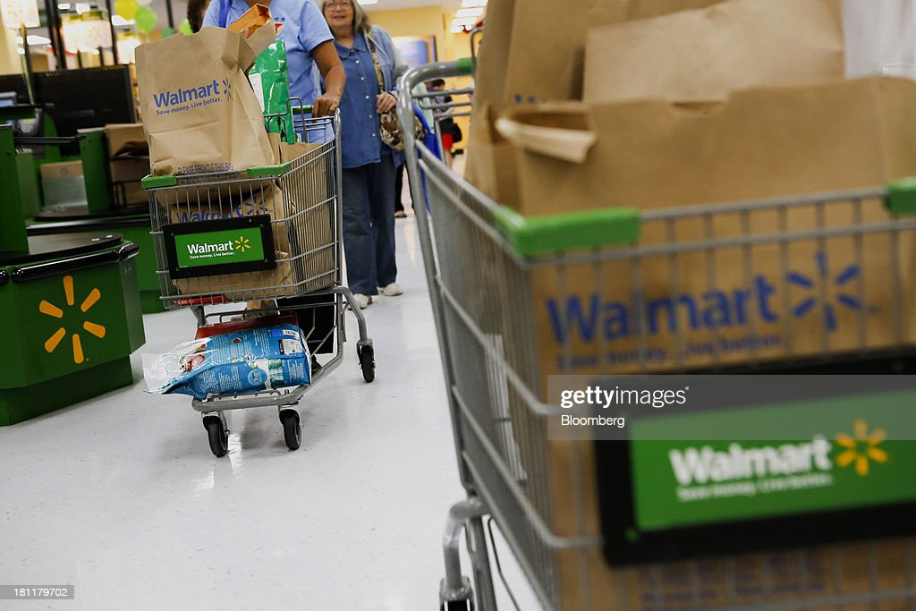 Customers push shopping carts carrying purchased groceries past a cash register during the grand opening of a Wal-Mart Stores Inc. location in the Chinatown neighborhood of Los Angeles, California, U.S., on Thursday, Sept. 19, 2013. Wal-Mart Stores Inc. will phase out 10 chemicals it sells in favor of safer alternatives and disclose the chemicals contained in four product categories, the company announced Sept. 12. Photographer: Patrick T. Fallon/Bloomberg via Getty Images