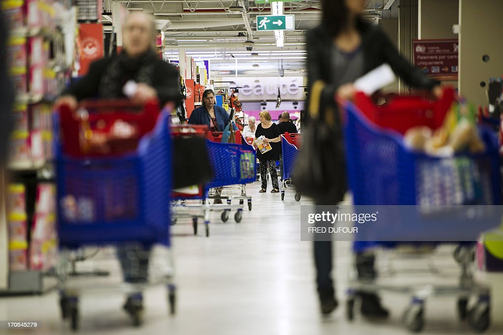 Customers push shopping carts in a Carrefour supermarket, on June 14, 2013 in Sainte-Geneviève-des-Bois, outside Paris. Installed in Sainte-Geneviève-des-Bois since fifty years, on June 15, 1963, this supermarket is the first of French giant retailer Carrefour group, but also the first in France.