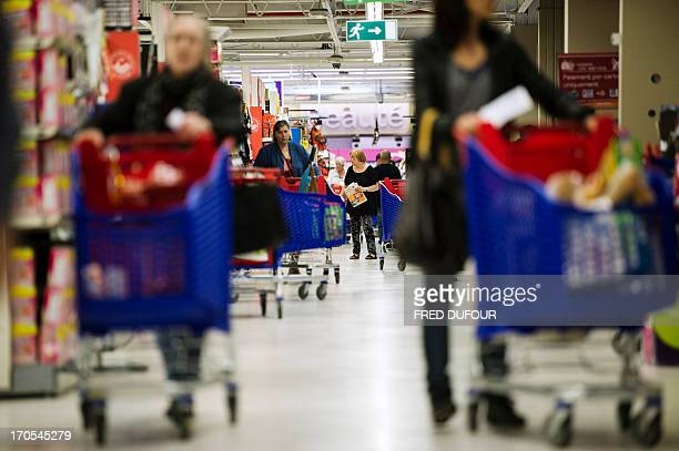 Customers push shopping carts in a Carrefour supermarket on June 14 2013 in SainteGenevièvedesBois outside Paris Installed in SainteGenevièvedesBois...