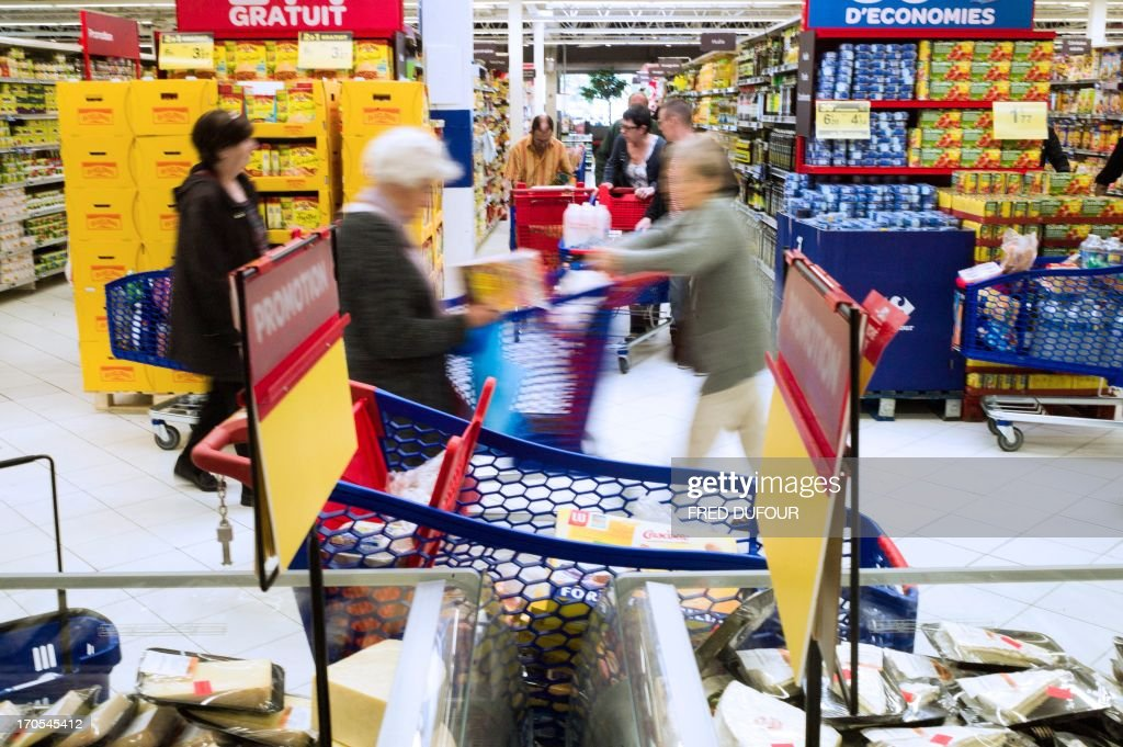 Customers push shopping carts in a Carrefour supermarket, on June 14, 2013 in Sainte-Geneviève-des-Bois, outside Paris. Installed in Sainte-Geneviève-des-Bois since fifty years, on June 15, 1963, this supermarket is the first of French giant retailer Carrefour group, but also the first in France. AFP PHOTO / FRED DUFOUR