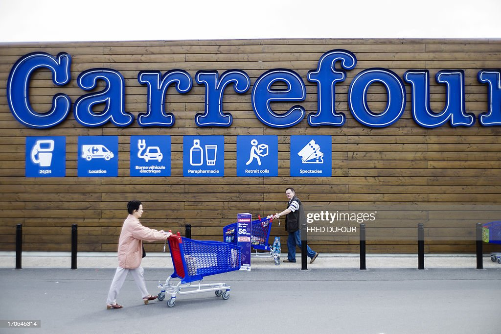 Customers push shopping carts outside a Carrefour supermarket, on June 14, 2013 in Sainte-Geneviève-des-Bois, near Paris. Installed in Sainte-Geneviève-des-Bois since fifty years, on June 15, 1963, this supermarket is the first of French giant retailer Carrefour group, but also the first in France. AFP PHOTO / FRED DUFOUR