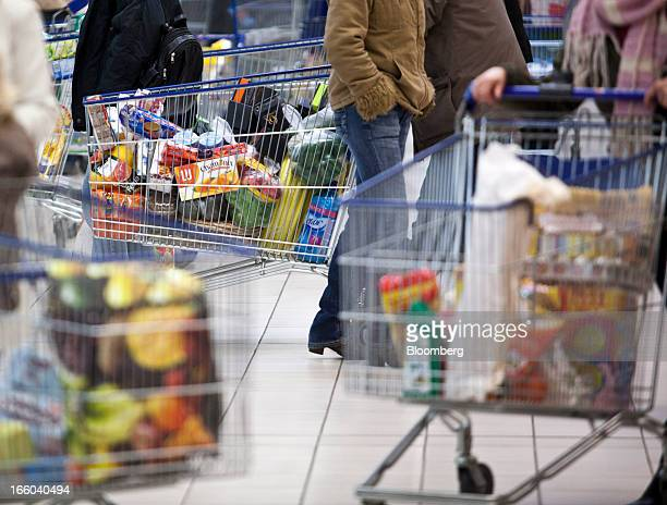 Customers push their shopping carts along the food aisles inside an E Leclerc hypermarket store in Villefranche de Rouergue France on Friday April 5...