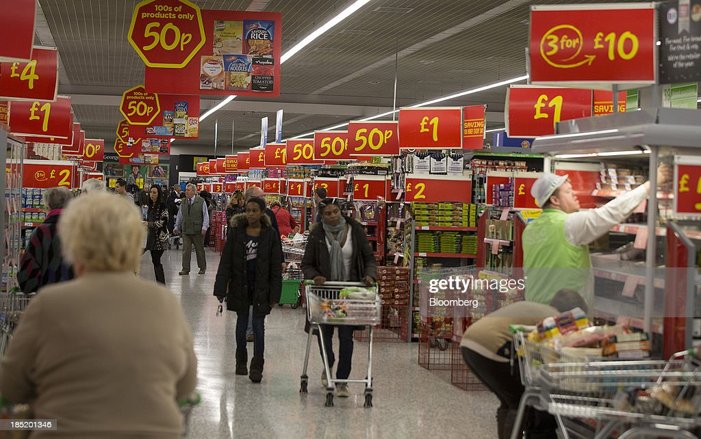 Customers push their shopping carts past giant signs advertising the cost of discounted goods inside an Asda supermarket, the U.K. retail arm of Wal-Mart Stores Inc., in Watford, U.K., on Thursday, Oct. 17, 2013. U.K. retail sales rose more than economists forecast in September as an increase in furniture demand led a rebound from a slump the previous month. Photographer: Simon Dawson/Bloomberg via Getty Images