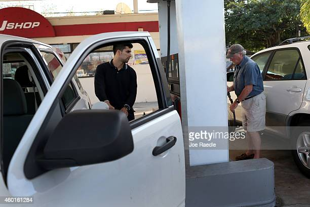 Customers put gas into their vehicle at the Ugas station on December 8 2014 in Miami Florida According to the AAA Monthly Gas Price Report todays...