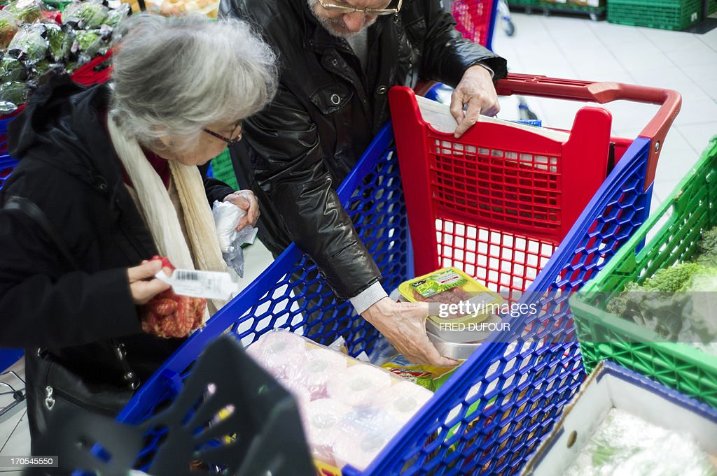 Customers put goods in their shopping cart in a Carrefour supermarket, on June 14, 2013 in Sainte-Geneviève-des-Bois, outside Paris. Installed in Sainte-Geneviève-des-Bois since fifty years, on June 15, 1963, this supermarket is the first of French giant retailer Carrefour group, but also the first in France. AFP PHOTO / FRED DUFOUR