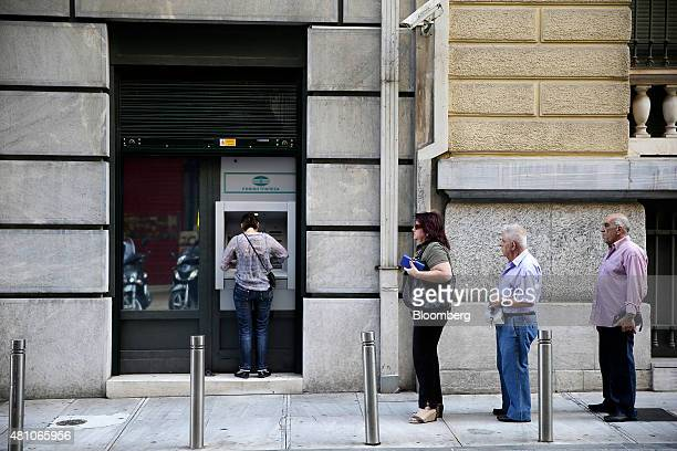 Customers queue along a street to use an automated teller machine operated by the National Bank of Greece SA in Athens Greece on Friday July 17 2015...