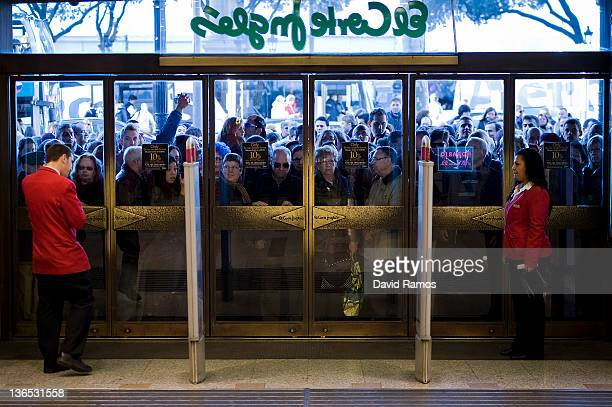 Customers queue at the entrance to El Corte Ingles department store before the doors are opened on the first day of the winter sales in Spain on...