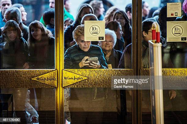 Customers queue at the entrance to El Corte Ingles department store before the doors are open on the first day of the winter sales on January 7 2015...