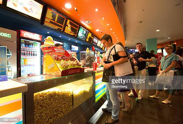 Customers queue at the snack counter in the foyer of the Cinema Park multiscreen movie theatre complex at the Metropolis Shopping and Entertainment...