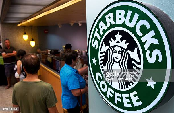 Customers queue for coffee at Starbucks Coffee inside the Dulles International Airport complex on August 30 2011 in Dulles Virginia near Washington...