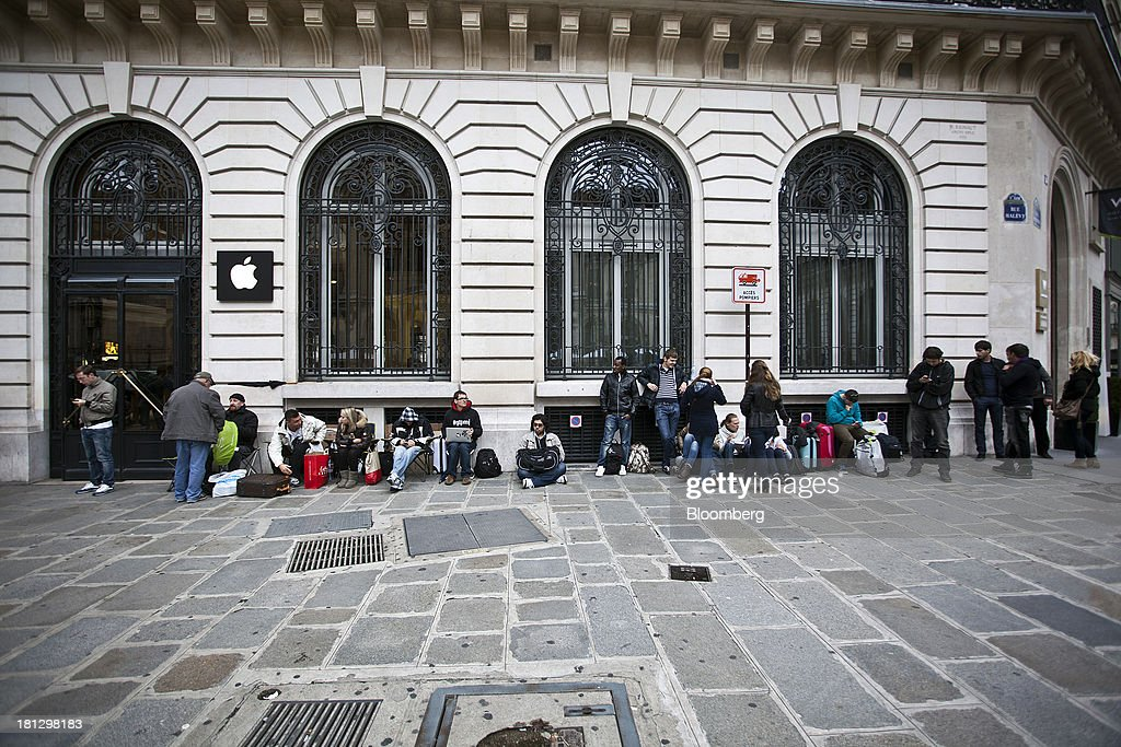 Customers queue for new iPhone 5s and 5c smartphones ahead of opening outside an Apple Inc. store in Paris, France, on Thursday, Sept. 19, 2013. Bank of France General Council member Bernard Maris said France will end up restructuring its debt as tax 'optimization' by large companies including Google Inc. will leave too big a burden on the middle class. Photographer: Balint Porneczi/Bloomberg via Getty Images