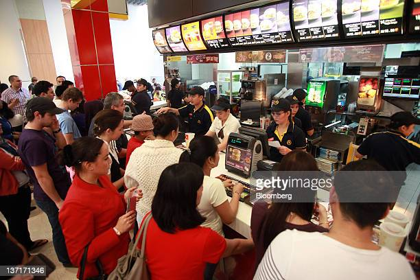 Customers queue for orders at the counter of a McDonald's Corp fastfood outlet in Dubai United Arab Emirates on Friday Jan 13 2012 Fastfood retailers...