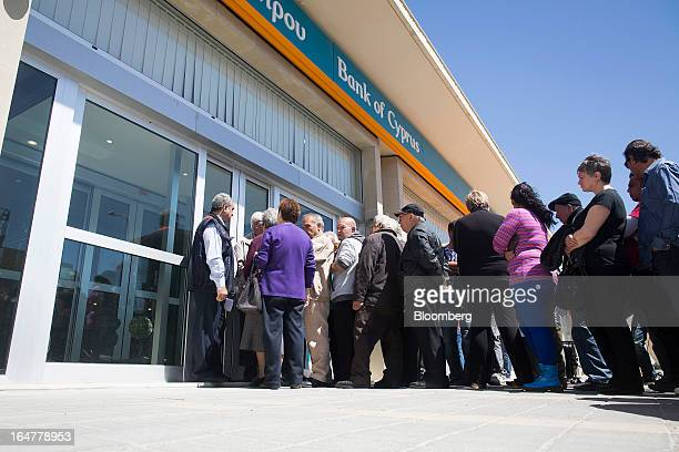 Customers queue outside a Bank of Cyprus Plc branch ahead of opening for the first time in two weeks in Nicosia Cyprus on Thursday March 28 2013 The...