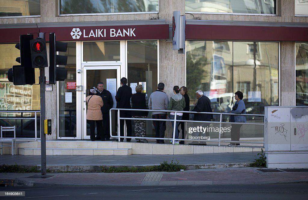 Customers queue outside a branch of Cyprus Popular Bank Pcl, also known as Laiki Bank, in Nicosia, Cyprus, on Friday, March 29, 2013. Cypriots face a second day of bank controls over their use of the euro as officials in Europe urged the country to move quickly to lift the restrictions, the first time they have been imposed on the common currency. Photographer: Simon Dawson/Bloomberg via Getty Images