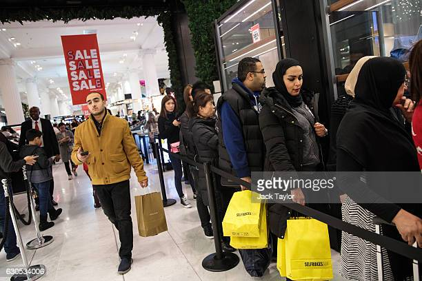 Customers queue outside a designer stall during the Boxing Day sale at Selfridges on December 26 2016 in London England Boxing Day is traditionally...
