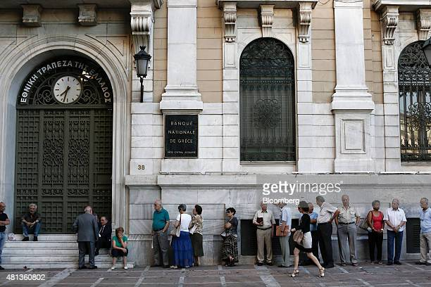 Customers queue outside a National Bank of Greece SA bank branch ahead of opening in Athens Greece on Monday July 20 2015 German Chancellor Angela...