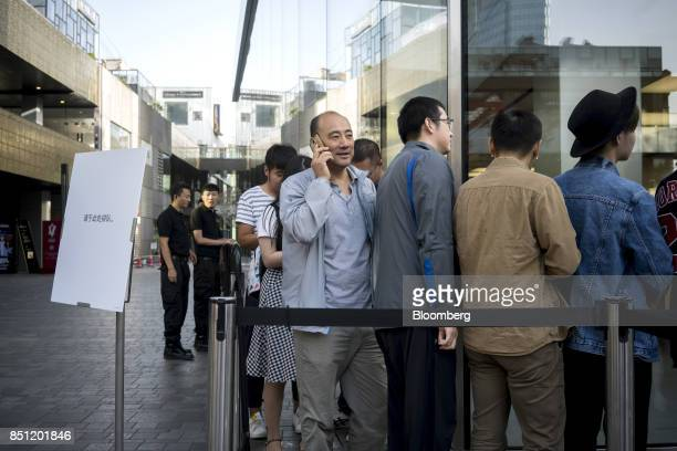 Customers queue outside the Apple Inc store at Sanlitun ahead of doors opening for the launch of the iPhone 8 in Beijing China on Friday Sept 22 2017...