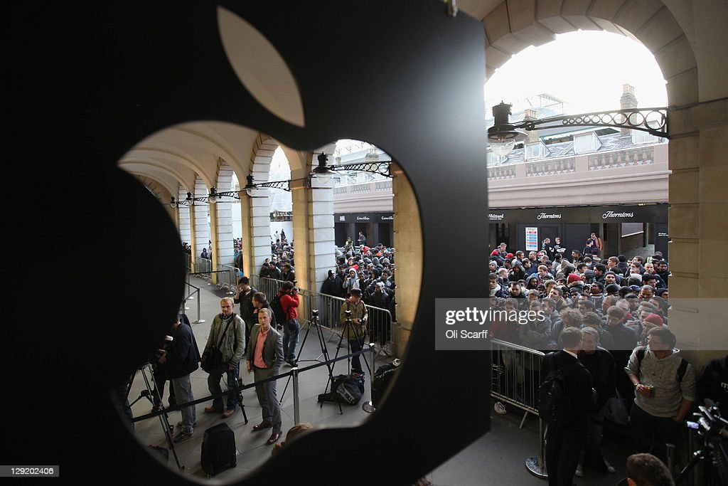 Customers queue outside the Apple store in Covent Garden to buy an iPhone 4S on October 14, 2011 in London, England. The widely anticipated new mobile phone from Apple has seen customers queue in cities around the world for hours to be amongst the first to buy the device.