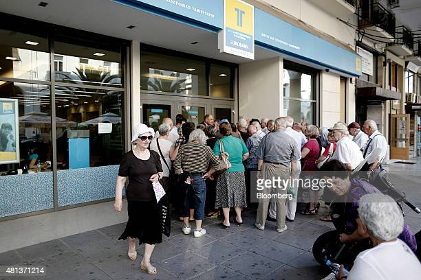 Customers queue to access a Eurobank Ergasias SA bank branch ahead of opening in Thessaloniki Greece on Monday July 20 2015 German Chancellor Angela...