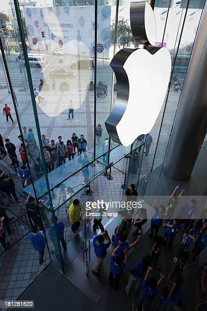 Customers queue to buy Apple's new iPhone 5c and 5s at the Wangfujing flagship store on September 20 2013 in Beijing ChinaApple launched the new...