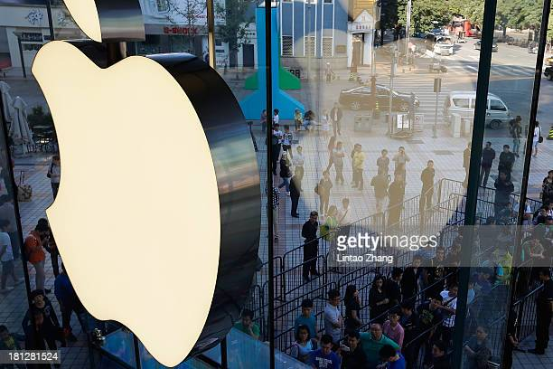 Customers queue to buy Apple's new iPhone 5c and 5s at the Wangfujing flagship store on September 20 2013 in Beijing China Apple launched the new...