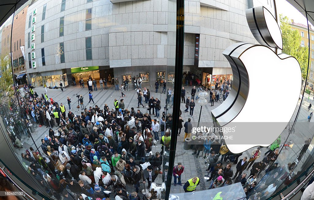Customers queue to enter the Apple Store where a giant logo is displayed in the southern German city of Munich on September 21, 2012 as the iPhone 5 goes on sale.