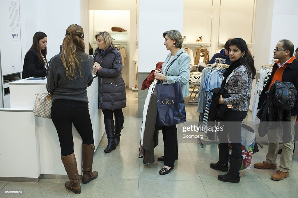 Customers queue to pay for purchases at a cash desk inside a Zara fashion store, operated by Inditex SA, in Madrid, Spain, on Tuesday, March 12, 2013. Europe's richest man, Amancio Ortega, the 76-year-old founder of Inditex SA, the world's biggest clothing retailer and owner of the Zara clothing chain, is No. 3 on Standard & Poor's 500 Index with a net worth of $57.4 billion, $4.9 billion ahead of Warren Buffett, 82. Photographer: Angel Navarrete/Bloomberg via Getty Images