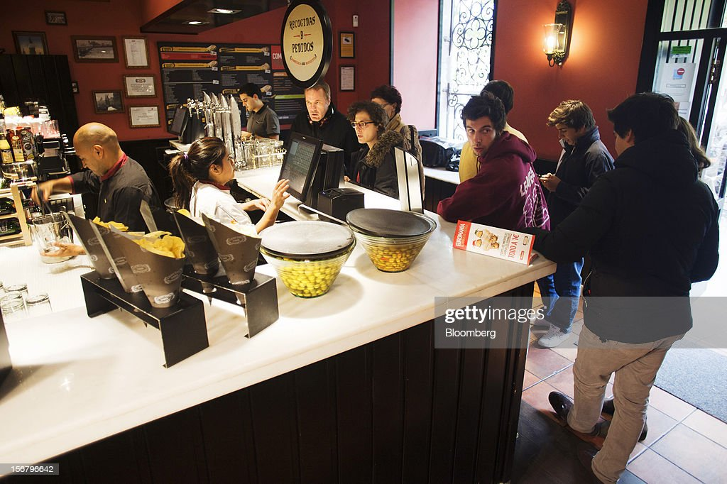 Customers queue to place food orders at the counter of a 100 Montaditos restaurant in Madrid, Spain, on Wednesday, Nov. 21, 2012. The Madrid-based chain in January opened its first U.S. restaurant in Miami and aims to have eight outlets in Florida by next March. Photographer: Angel Navarrete/Bloomberg via Getty Images