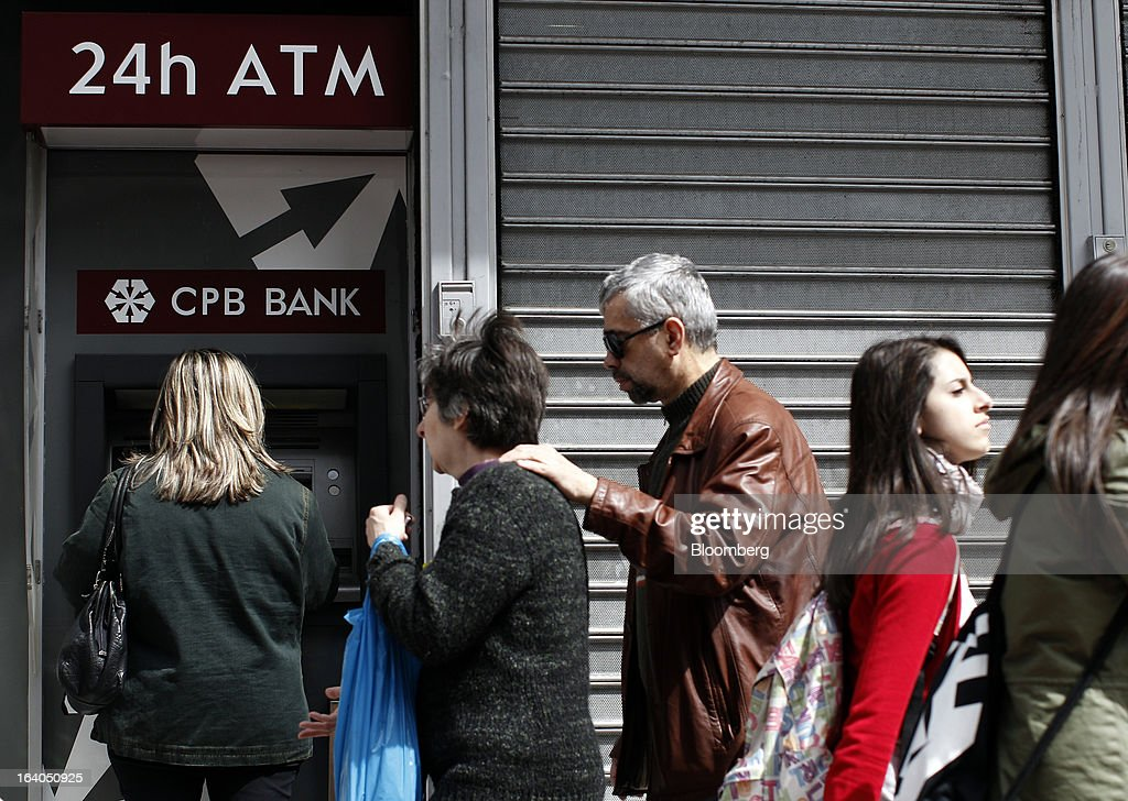 Customers queue to use a 24-hour automated teller machine (ATM) operated by CPB Bank, part of Cyprus Popular Bank Plc, in Athens, Greece, on Tuesday, March 19, 2013. Cyprus's passage of an unprecedented levy on bank deposits was in doubt as euro-area finance ministers responded to criticism of the measure by loosening their stance on how the money is raised. Photographer: Kostas Tsironis/Bloomberg via Getty Images