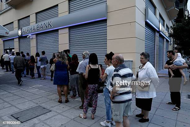 Customers queue to use an automated teller machine outside a Alpha Bank branch in Thessaloniki Greece on Sunday June 28 2015 Greece moved to avert...