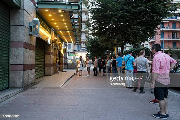 Customers queue to use an automated teller machine outside a Piraeus Bank SA bank branch in Thessaloniki Greece on Saturday June 27 2015 Greek...