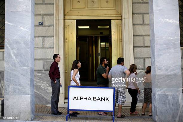 Customers queue to use an automated teller machine outside an open Alpha Bank AE bank branch in Athens Greece on Monday July 20 2015 German...