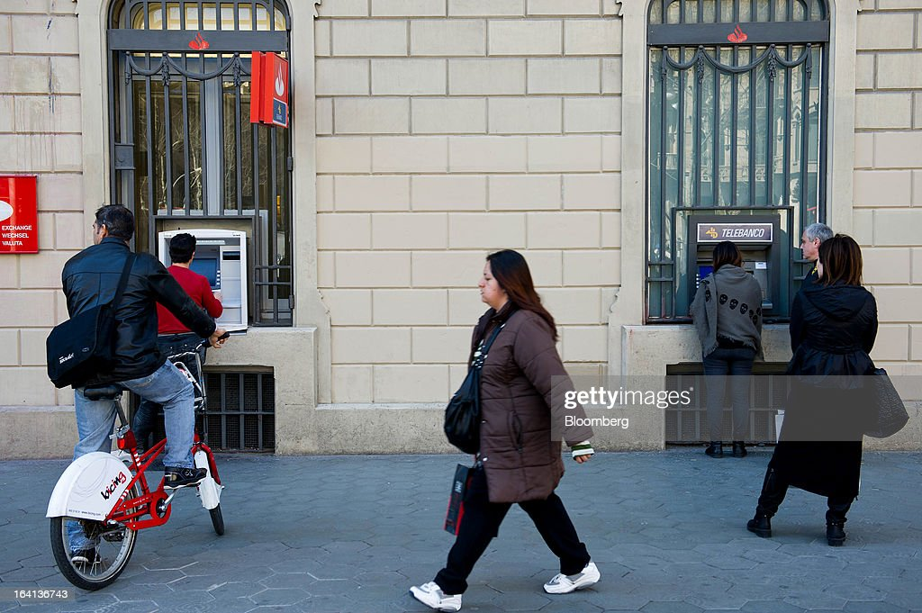 Customers queue to use automated teller machines (ATM) outside a Banco Santander SA branch in Barcelona, Spain, on Wednesday, March 20, 2013. Officials from the troika of international creditors -- the ECB, the International Monetary Fund and the European Commission -- are in Cyprus discussing further capital controls and possibly extending a bank holiday to the end of the week, a European official familiar with the talks said on condition of anonymity because the discussions are confidential. Photographer: David Ramos/Bloomberg via Getty Images