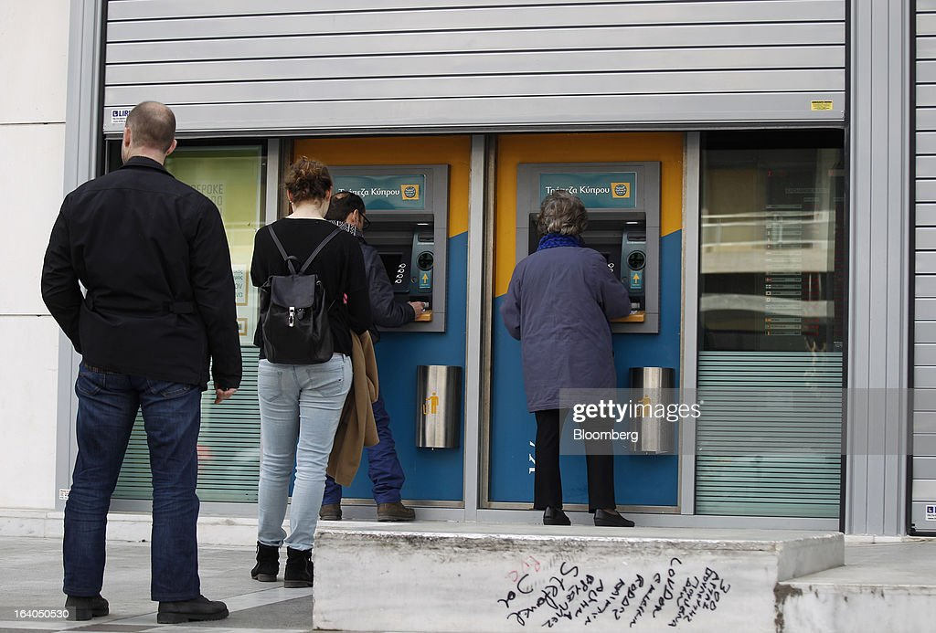Customers queue to use automated teller machines (ATM) outside a closed bank branch at the headquarters of the Bank of Cyprus Plc in Athens, Greece, on Tuesday, March 19, 2013. Cyprus's passage of an unprecedented levy on bank deposits was in doubt as euro-area finance ministers responded to criticism of the measure by loosening their stance on how the money is raised. Photographer: Kostas Tsironis/Bloomberg via Getty Images