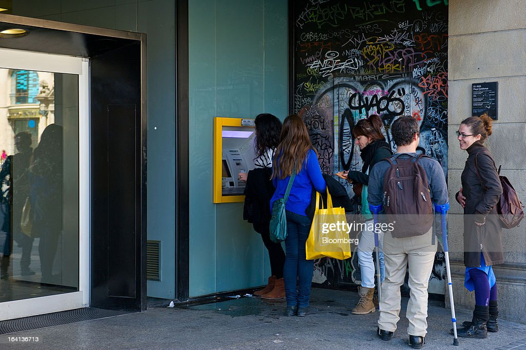 Customers queue to withdraw cash from an automated teller machine (ATM) outside a CaixaBank SA branch in Barcelona, Spain, on Wednesday, March 20, 2013. Officials from the troika of international creditors -- the ECB, the International Monetary Fund and the European Commission -- are in Cyprus discussing further capital controls and possibly extending a bank holiday to the end of the week, a European official familiar with the talks said on condition of anonymity because the discussions are confidential. Photographer: David Ramos/Bloomberg via Getty Images