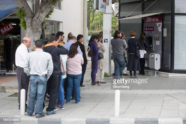 Customers queue to withdraw cash from an automated teller machine outside a Cyprus Popular Bank Pcl also known as Laiki Bank in Limassol Cyprus on...
