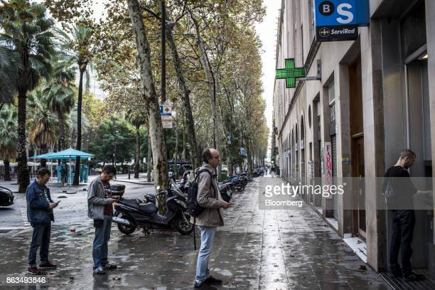 Customers queue to withdraw cash from an automated teller machine outside a Banco de Sabadell SA bank branch in Barcelona Spain on Friday Oct 20 2017...