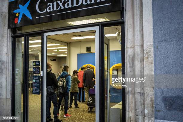 Customers queue to withdraw cash from an automated teller machine inside a CaixaBank SA bank branch in Barcelona Spain on Friday Oct 20 2017 In a...