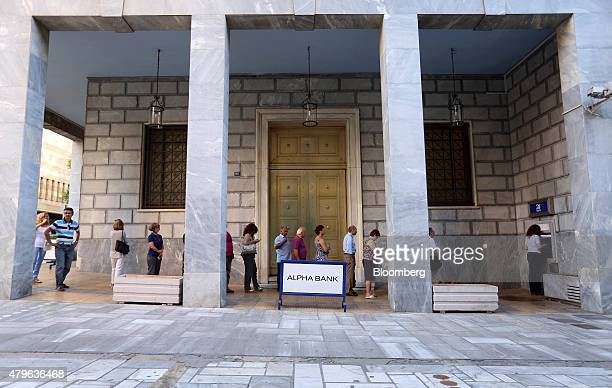 Customers queue to withdraw cash from an automated teller machine outside an Alpha Bank AE bank branch in Athens Greece on Monday July 6 2015...