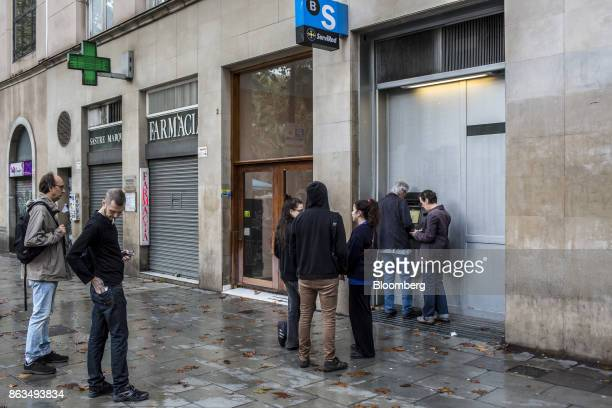 Customers queue to withdraw cash from an automated teller machine operated by Banco de Sabadell SA bank in Barcelona Spain on Friday Oct 20 2017 In a...