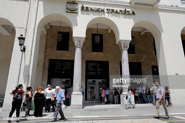 Customers queue to withdraw cash from automated teller machines outside a main branch of the National Bank of Greece SA in Thessaloniki Greece on...