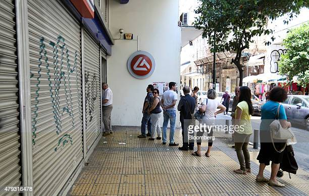 Customers queue to withdraw cash from automated teller machines outside a closed and shuttered Eurobank Ergasias SA bank branch in Athens Greece on...