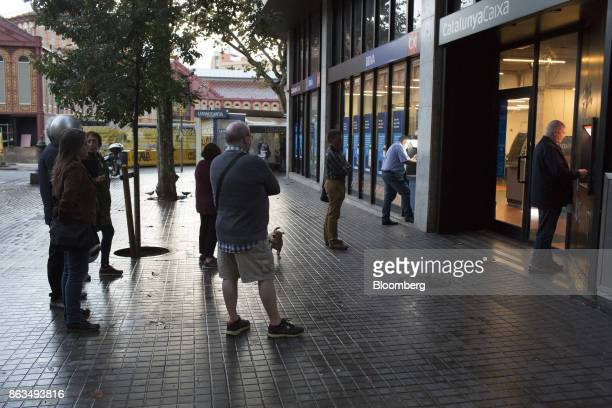 Customers queue to withdraw cash from automated teller machines operated by Catalunya Bank SA left and Banco Bilbao Vizcaya Argentaria SA in...
