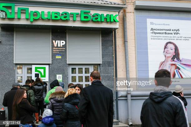 Customers queue to withdraw hryvnia currency from an automated teller machine outside a Privatbank CJSC bank branch in Kiev Ukraine on Thursday Feb...