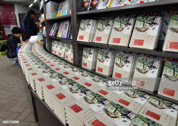 Customers read books by Japanese author Haruki Murakami as Murakami's new novels of the book 'Onna no Inai Otokotachi' which can be translated as...
