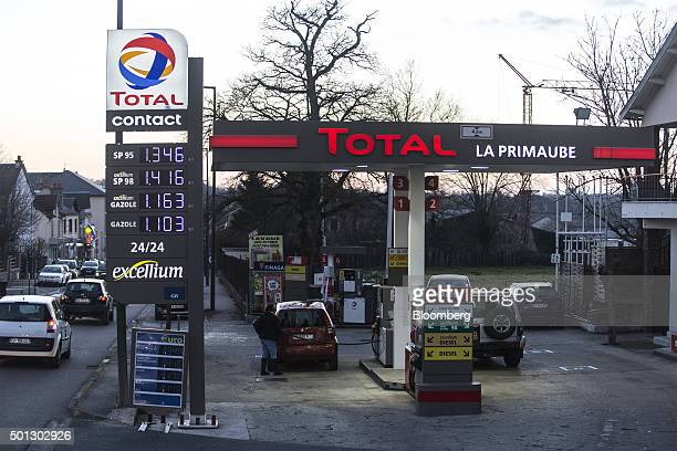 Customers refuel their automobiles on the forecourt of a gas station operated by Total SA in LucLaPrimaube near Rodez France on Friday Dec 11 2015...