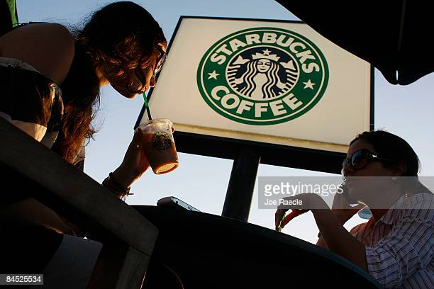 Customers relax and drink their beverages at a Starbucks Coffee shop on January 28 2009 in Miami Florida Starbucks will lay off about 700 nonstore...
