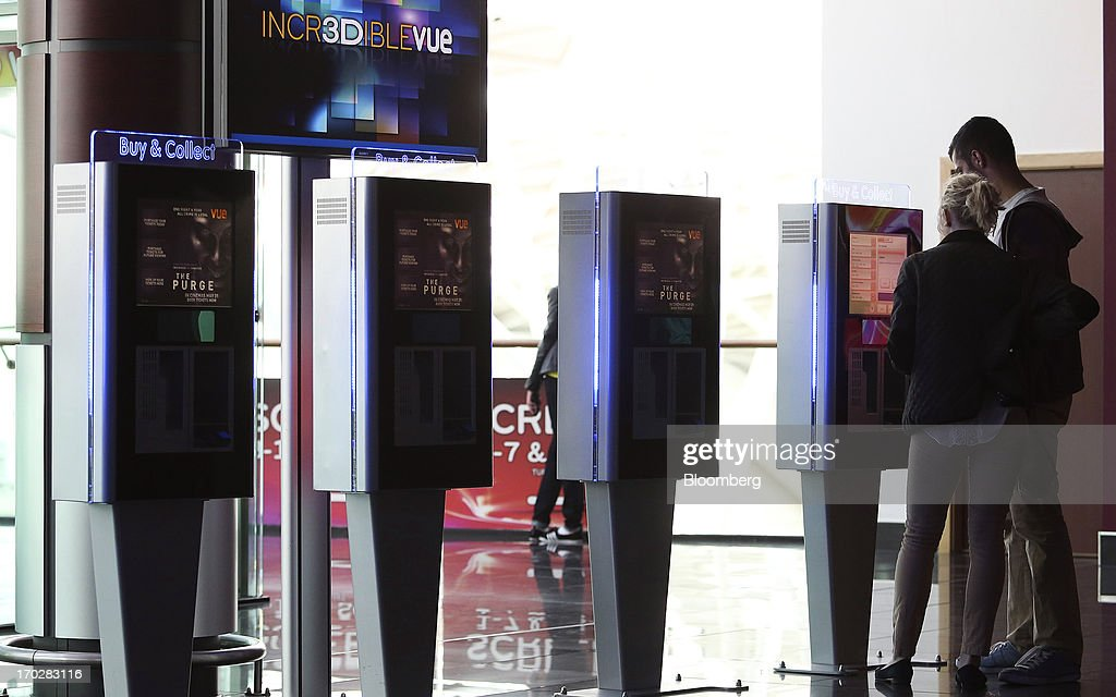 Customers retrieve tickets at a self-serve machine inside a Vue Cinema, operated by Vue Entertainment Ltd., at the Westfield Stratford City retail complex in London, U.K., on Tuesday, June 4, 2013. Vue Entertainment Ltd., the U.K. cinema chain bought by private equity firm Doughty Hanson & Co., are continuing to expand in Europe, recently aquiring Poland's second-largest cinema chain Multikino. Photographer: Chris Ratcliffe/Bloomberg via Getty Images
