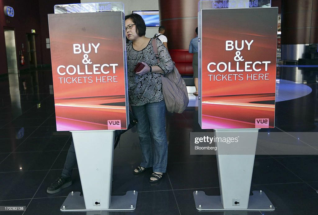 Customers retrieve tickets at a self-serve machine inside a Vue Cinema, operated by Vue Entertainment Ltd., at the Westfield Stratford City retail complex in London, U.K., on Tuesday, June 4, 2013. Vue Entertainment, the U.K. cinema chain bought by private equity firm Doughty Hanson & Co., are continuing to expand in Europe, recently acquiring Poland's second-largest cinema chain Multikino. Photographer: Chris Ratcliffe/Bloomberg via Getty Images